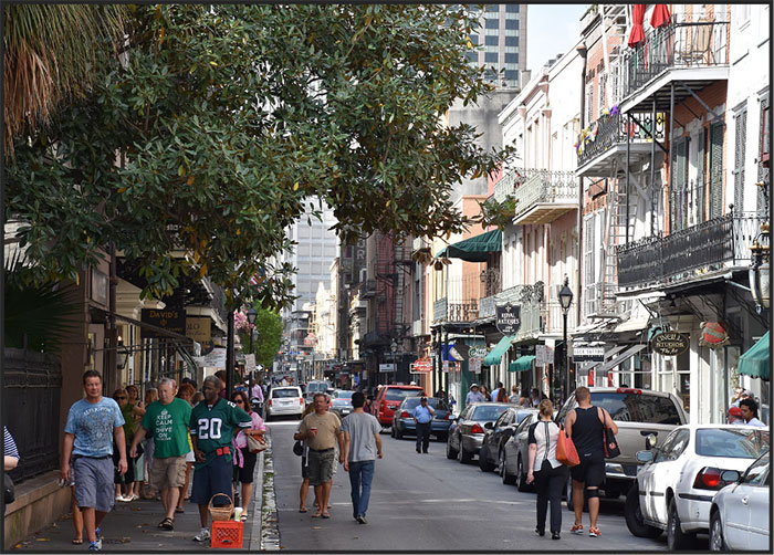 New Orleans street with pedastrians and cars shaded by trees and historic buildings with balconies.