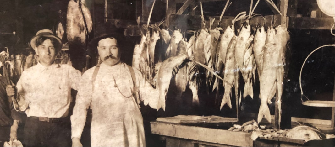 Paul Piazza standing with rabbit and fish